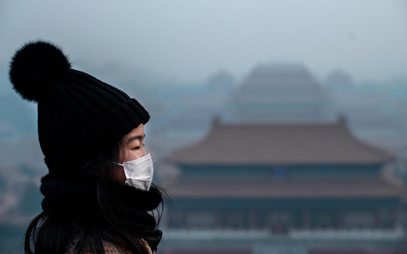 A woman wears a protective mask on January 26 as she stands on an overlook near Beijing's Forbidden City.
